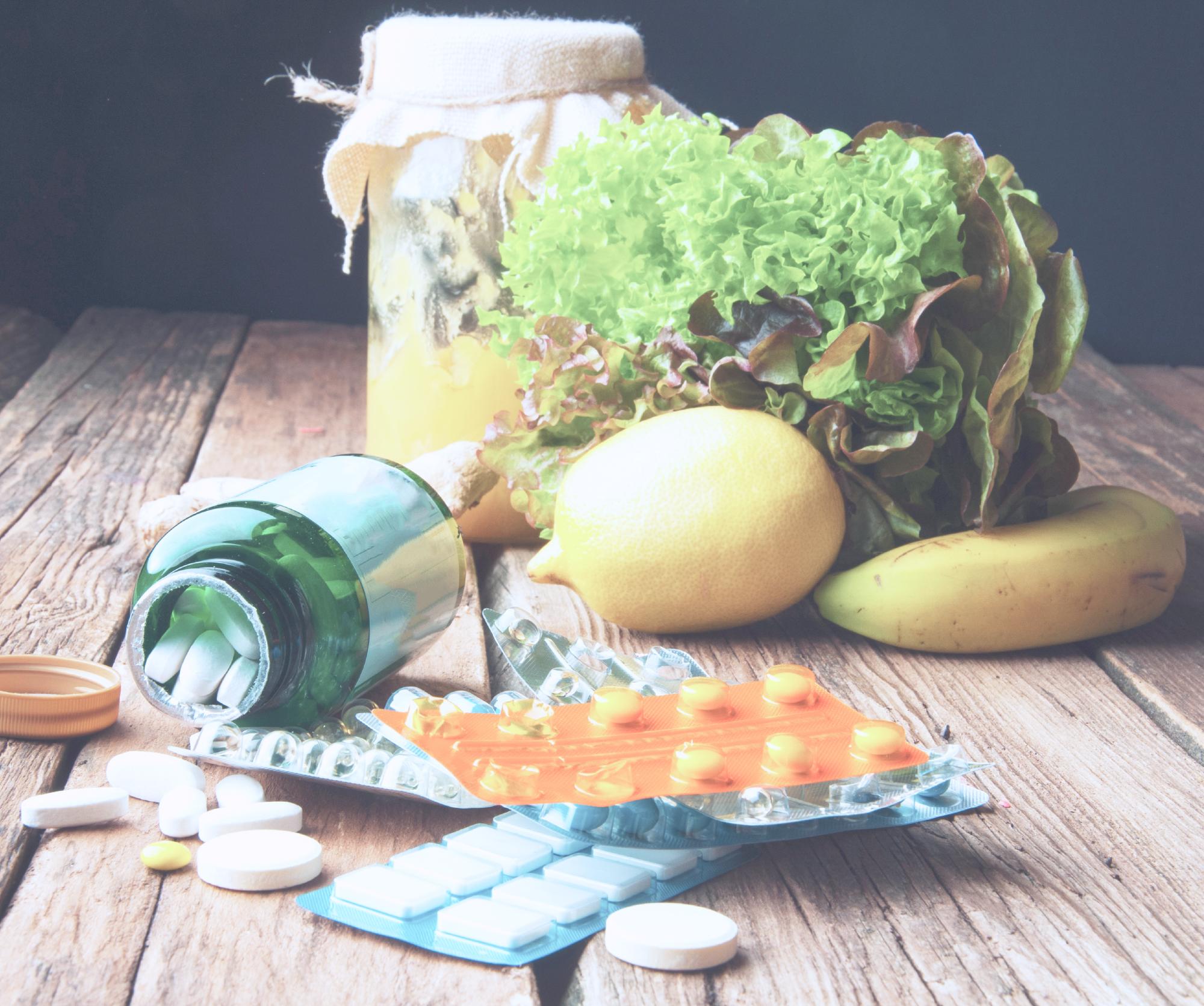 在木桌上有檸檬和香蕉還有綠色植物跟藥片,玻璃罐裝灑落一些錠劑。