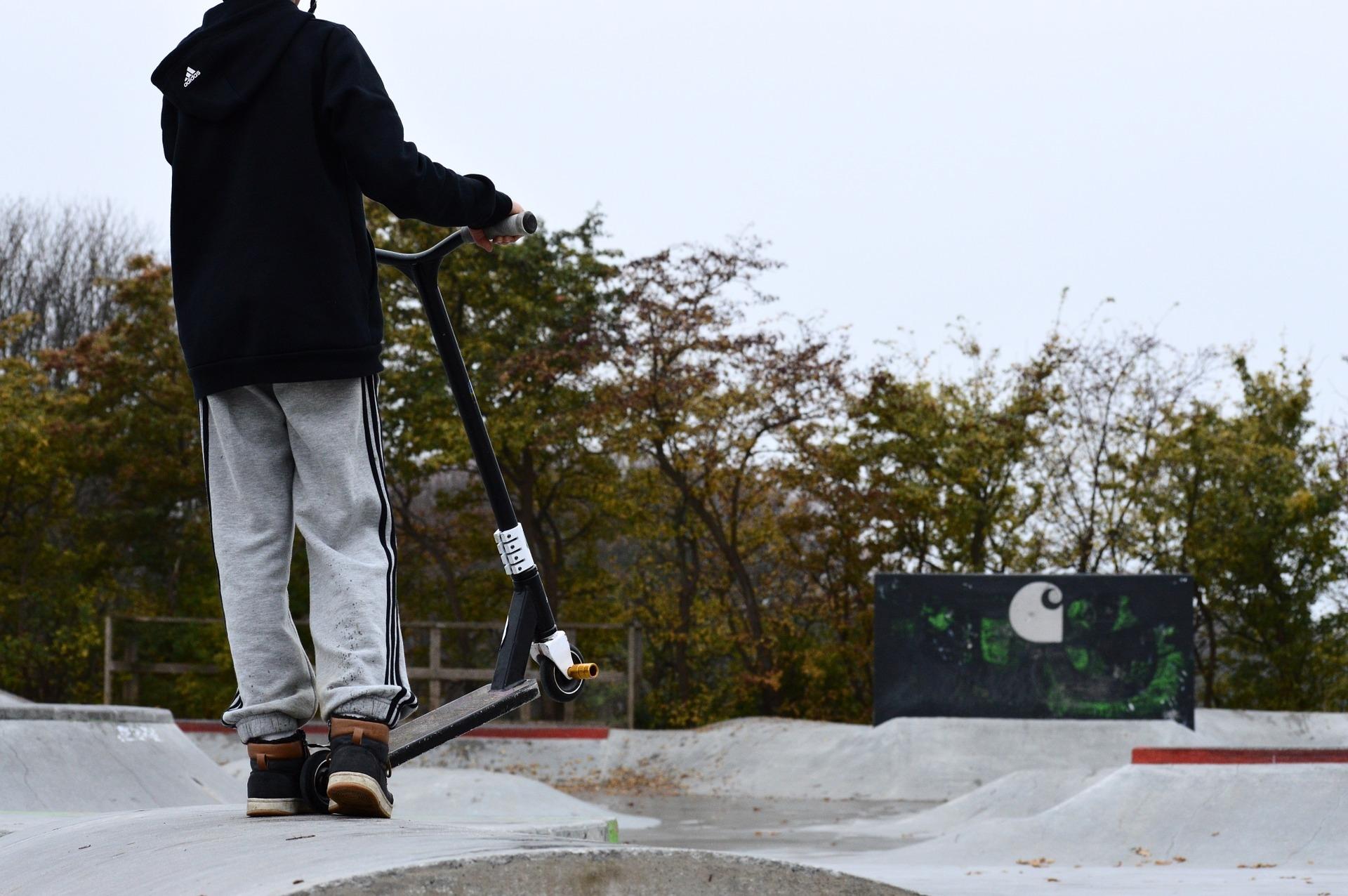 一個人在滑行場拿著電動滑板車