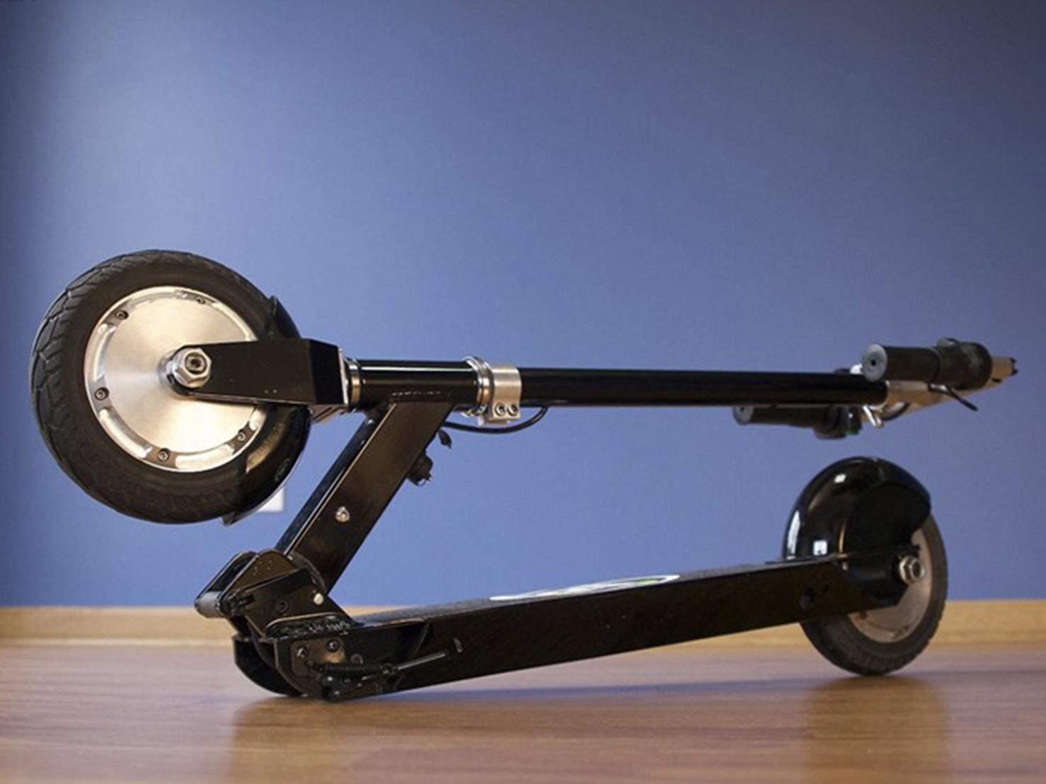 摺疊起來並放在地上的電動滑板車