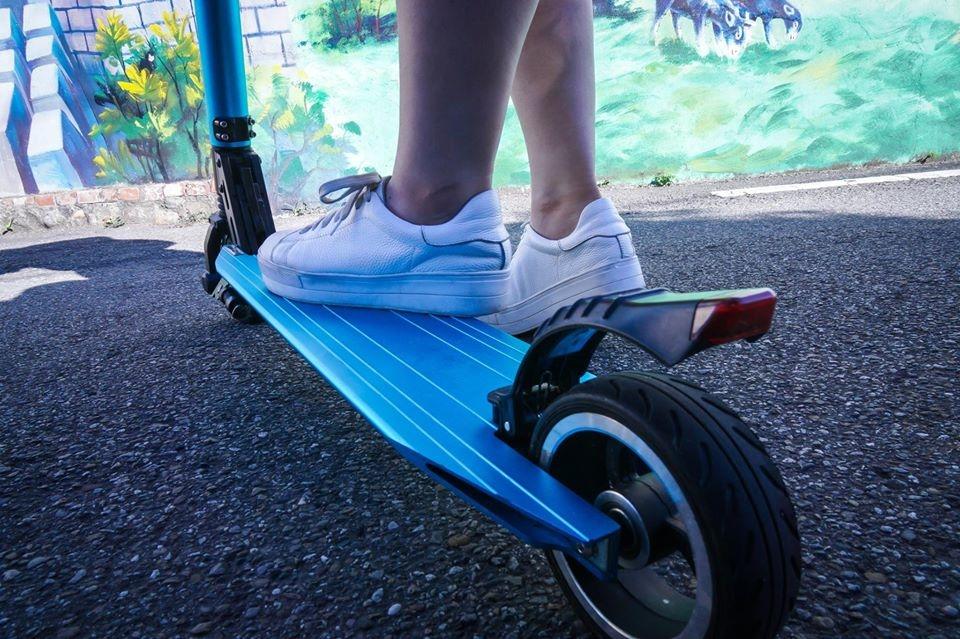 踩著藍色鋁合金電鍍滑板車的腳