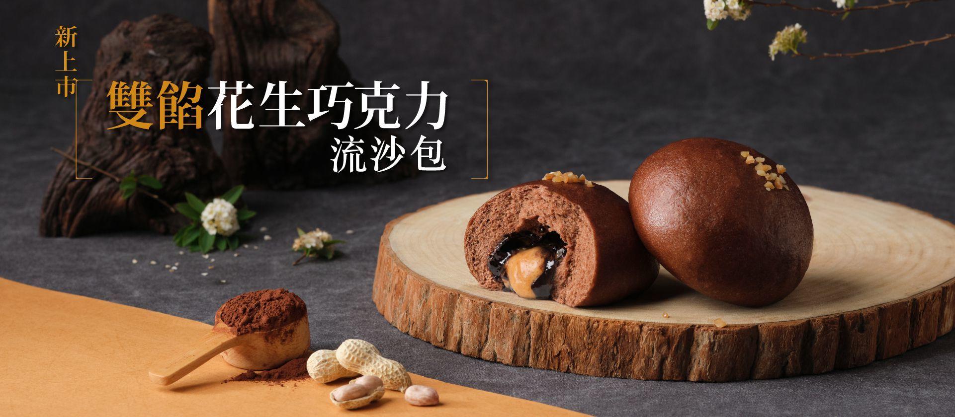 兩顆深咖啡色的花生巧克力流沙包陳列在木質圓盤上,其中一顆被剝開,流出花生與巧克力的內餡。畫面前方有一匙可可粉以及剝開的帶殼花生。